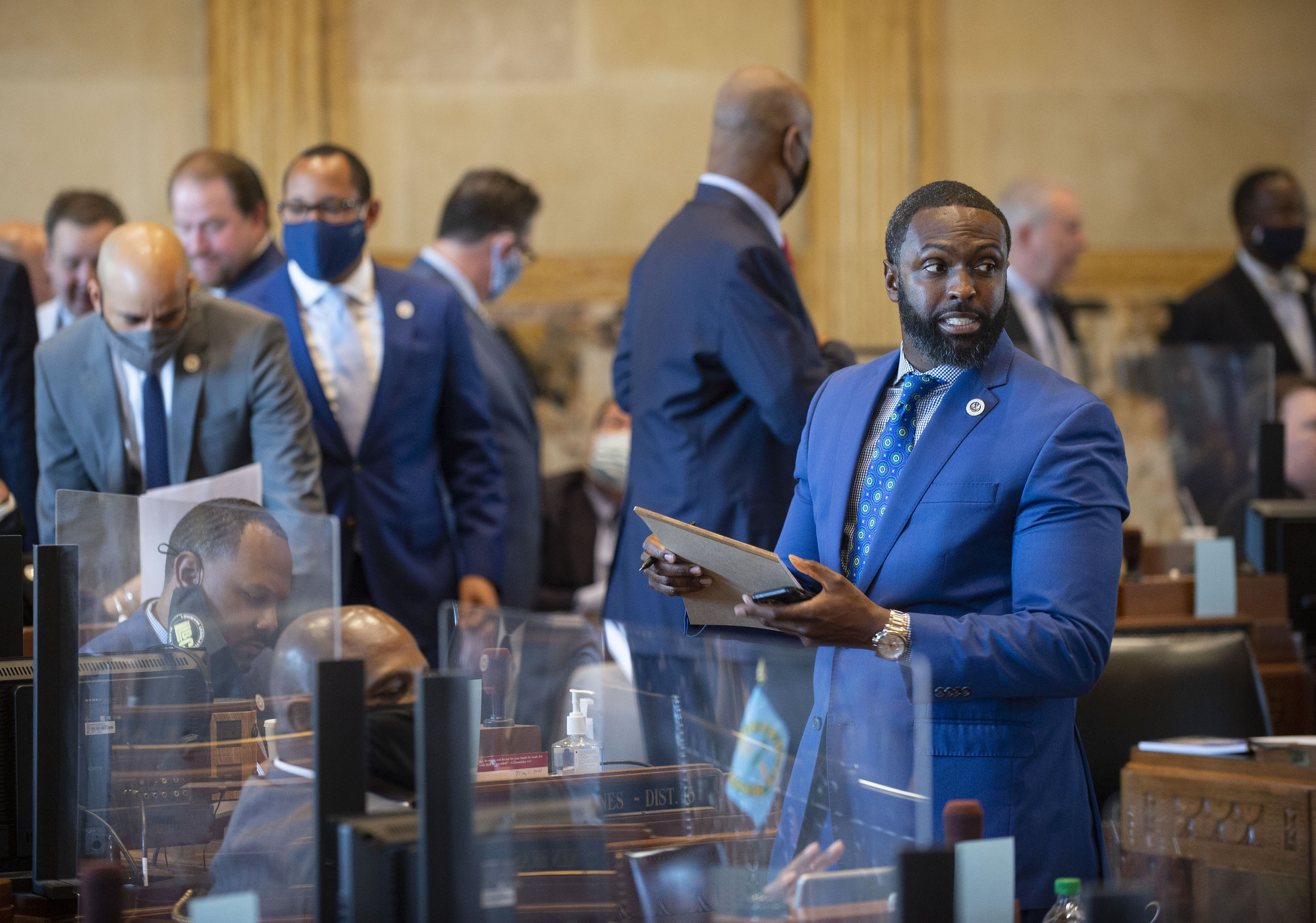 Louisiana state Rep. Ted James, D-Baton Rouge, right, and other representatives talk on the House floor on April 12, 2021, at the Capitol. (Photo by Travis Spradling, The Advocate)